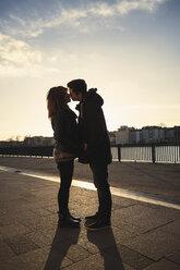 Germany, Berlin, teenage couple kissing on a promenade along a lake - MMFF000525