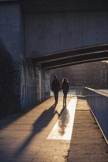 Germany, Berlin, teenage couple walking under a bridge at evening sunlight - MMFF000527