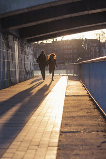 Germany, Berlin, teenage couple running under a bridge at evening sunlight - MMFF000518