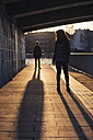 Germany, Berlin, teenage couple standing under a bridge at evening sunlight - MMFF000519