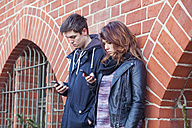 Teenage couple standing in front of a brick house using smartphones - MMFF000514