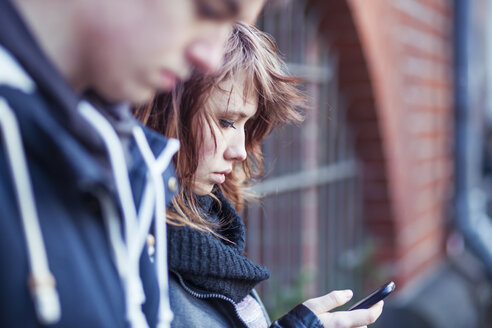 Teenage girl with smartphone, boy blurred in the foreground - MMFF000511