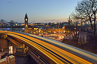 Germany, Hamburg, Clocktower at Landungsbruecken and light tracks of a subway at sunset - RJ000413