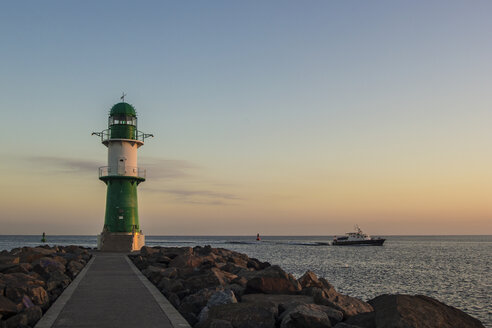 Germany, Warnemuende, lighthouse in early morning with a boat coming in - MELF000046