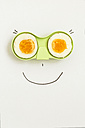 Two halves of an egg in green holder with happy face drawn around it - MELF000048