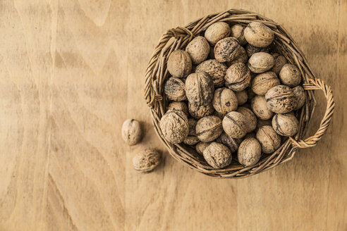 Basket full of walnuts on wooden ground - MELF000052