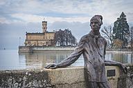 Germany, Baden-Wuerttemberg, Langenargen, Bronze sculpture Dammglonker by Roland Martin, Montfort Castle in the background - KEB000058