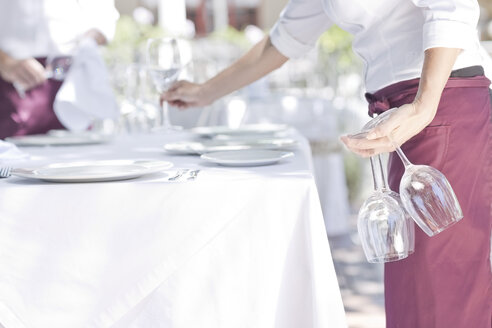 Waiter placing wine glasses on outdoor restaurant table - ZEF004024
