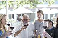 Extended family drinking red wine at restaurant - ZEF004097