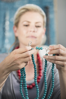 Woman inspecting a bead necklace - ZEF003648