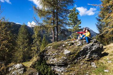 Austria, Altenmarkt-Zauchensee, young couple sitting on a rock looking at view - HHF005156