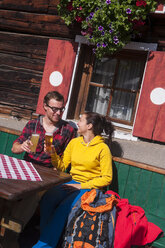 Austria, Altenmarkt-Zauchensee, young couple with beer glasses sitting in front of Alpine cabin - HHF005158