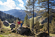 Austria, Altenmarkt-Zauchensee, young couple standing on a rock looking at view - HHF005178