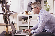 Businessman working with laptop at home office - SEGF000266