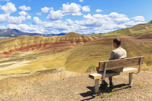 USA, Oregon, John Day Fossil Beds National Monument, tourist sitting on a bench looking at Painted Hills - FOF007812