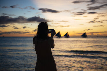 Philippines, Boracay, woman taking a picture of sunset with sailing boats - GEMF000123
