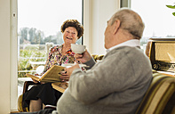 Senior couple with photo album drinking coffee at home - UUF003557