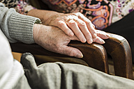Hands of senior couple on arm rest - UUF003567