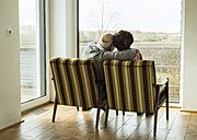 Senior couple sitting side by side in arm chairs looking through window - UUF003569