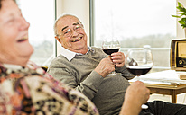 Senior man with glass of red wine - UUF003580