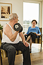 Senior man with dumbbell at home - UUF003652