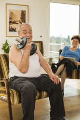 Senior man with dumbbell at home - UUF003651