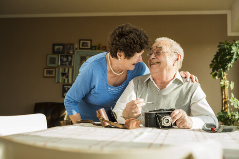 Senior couple with old camera at home - UUF003591