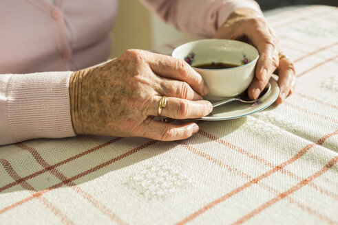 Hands of senior woman holding cup of coffee - UUF003599