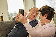 Senior couple taking a selfie with smartphone at home - UUF003612