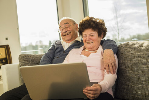 Senior couple using laptop at home - UUF003614