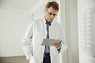 Mature man in lab coat using digital tablet - MFF001519