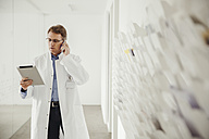 Mature man in lab coat on phone looking at digital tablet - MFF001521