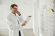 Smiling mature man in lab coat on phone looking at digital tablet - MFF001523