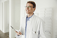 Smiling mature man in lab coat holding digital tablet - MFF001529