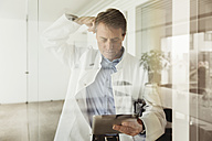 Mature man in lab coat using digital tablet behind glass pane - MFF001532