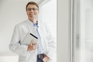 Smiling mature man in lab coat holding digital tablet at the window - MFF001539