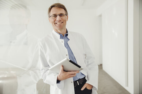 Smiling mature man in lab coat holding digital tablet - MFF001541