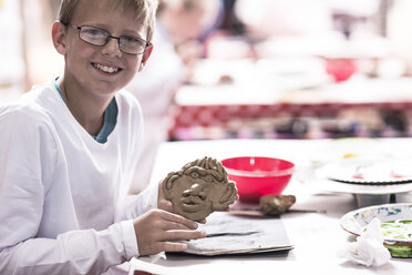 Smiling boy making face from modeling clay in art class at school - ZEF006135