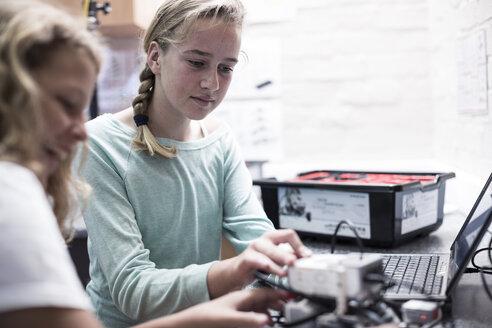 Two schoolgirls with laptop in robotics class - ZEF006094