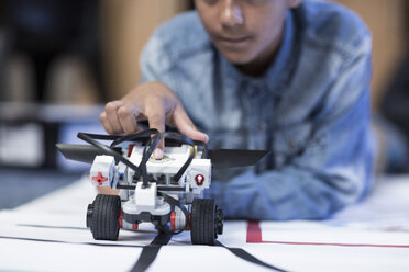 Schoolboy in robotics class testing vehicle on test track - ZEF006096