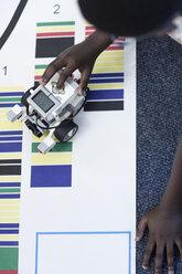 Schoolboy in robotics class testing vehicle on test track - ZEF006098