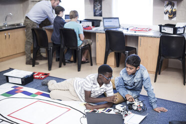 Schoolboys in robotics class testing vehicle on test track - ZEF006101