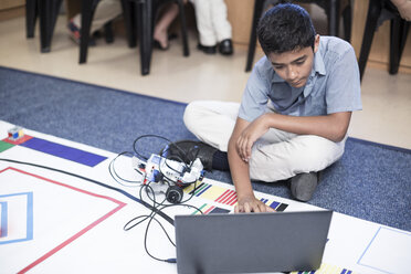 Schoolboy with laptop in robotics class testing vehicle on test track - ZEF006107