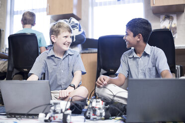 Two smiling schoolboys with laptops in robotics class - ZEF006110