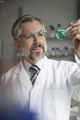 Scientist in laboratory examining liquid in round bottom flask - RBF002533