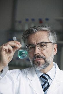 Scientist in laboratory examining liquid in round bottom flask - RBF002544
