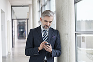 Businessman leaning against column using smartphone - RBF002561