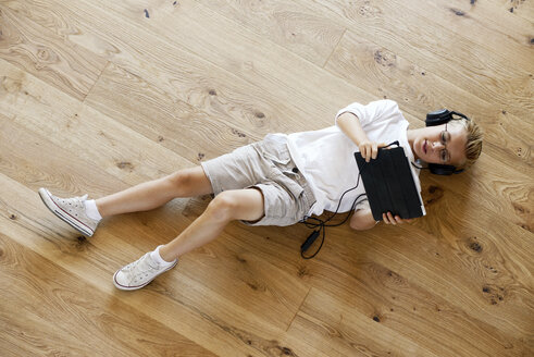 Boy lying on wooden floor using digital tablet - LBF001080