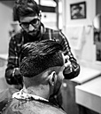Hairdresser cutting young man's hair in a barbershop - MGOF000144