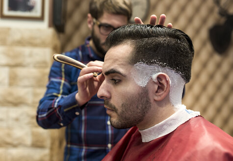 Hairdresser shaving young man's hair in a barbershop - MGOF000134